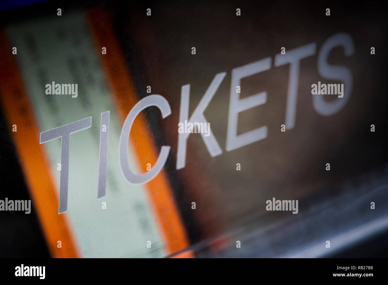 A train ticket awaits collection inside a ticket vending machine located at a UK train station. - Stock Image