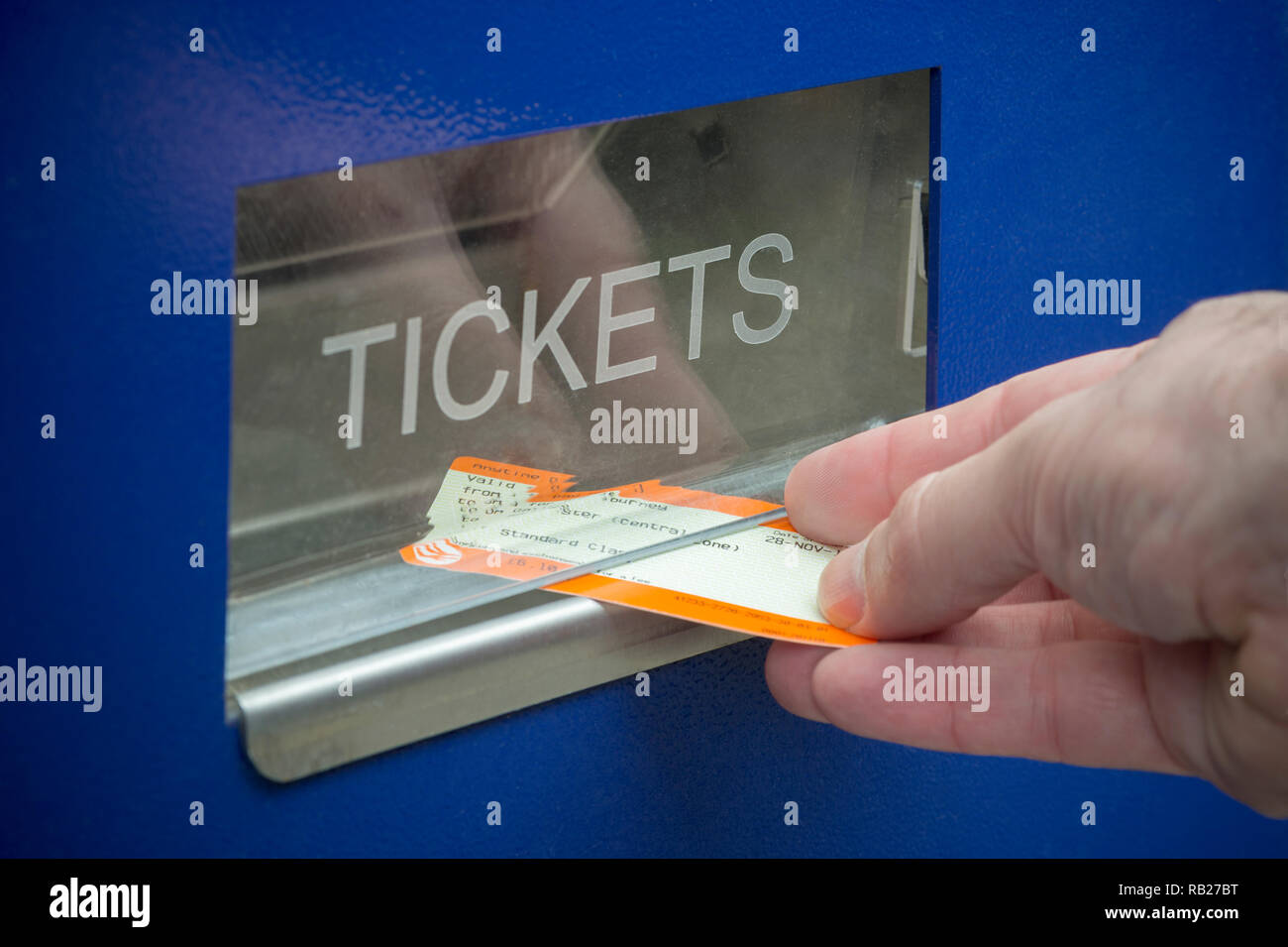 A man collects a train ticket from a ticket vending machine located at a UK train station. - Stock Image