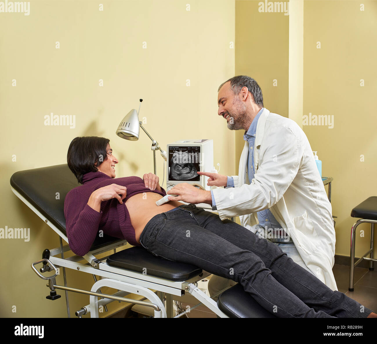 A smiling Gynecologist doing an ultrasound scan procedure on a happy fortyish Hispanic pregnant woman with a medical ultrasound scanner. - Stock Image