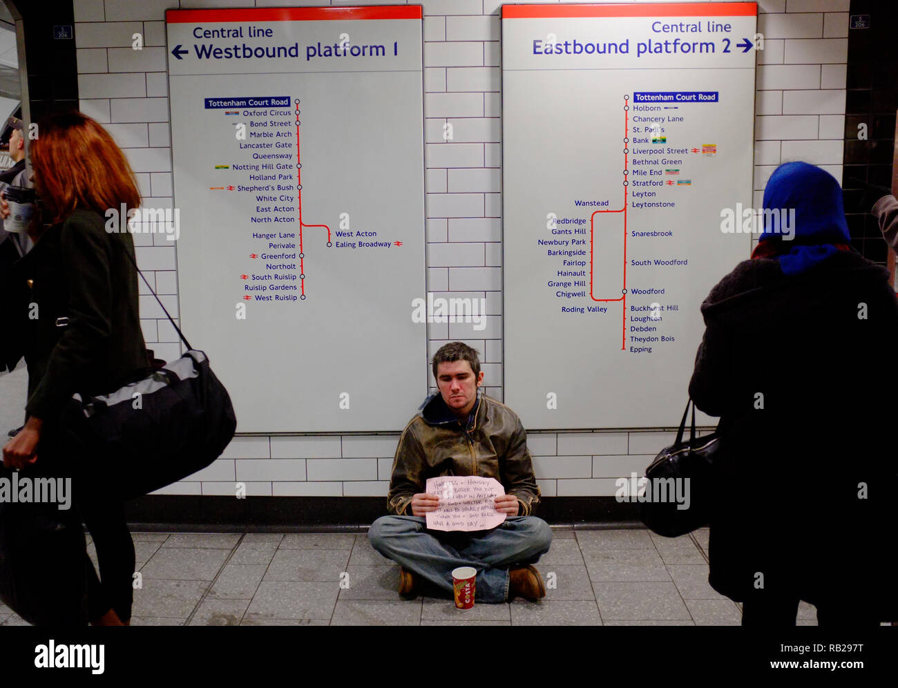 a young young, troubledhomeless man sits near the platforms of the central line on the london underground asking for help during the winter months - Stock Image