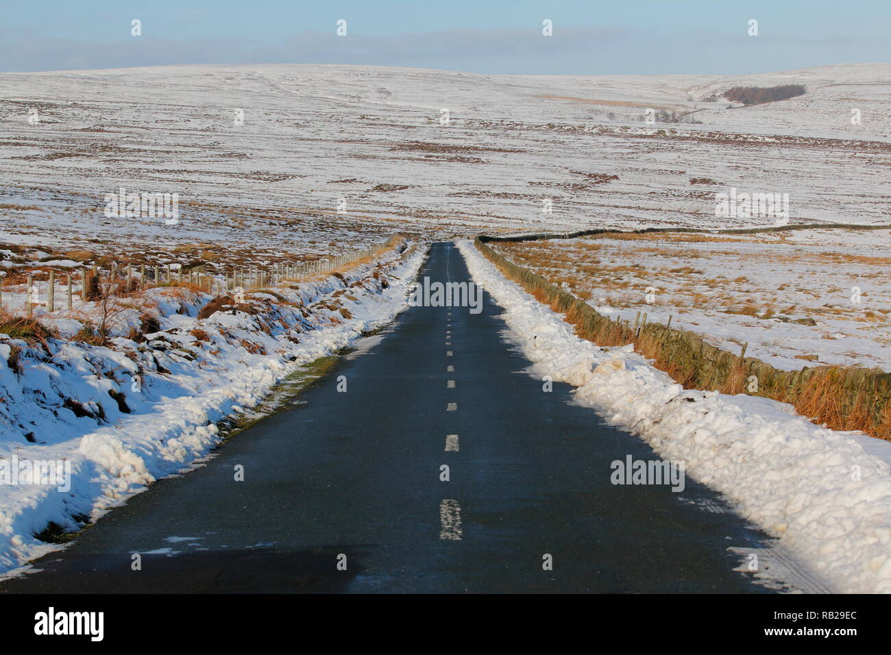 A country road in the Peak District National Park that has been cleared of snow to allow motorists to pass through safely. - Stock Image