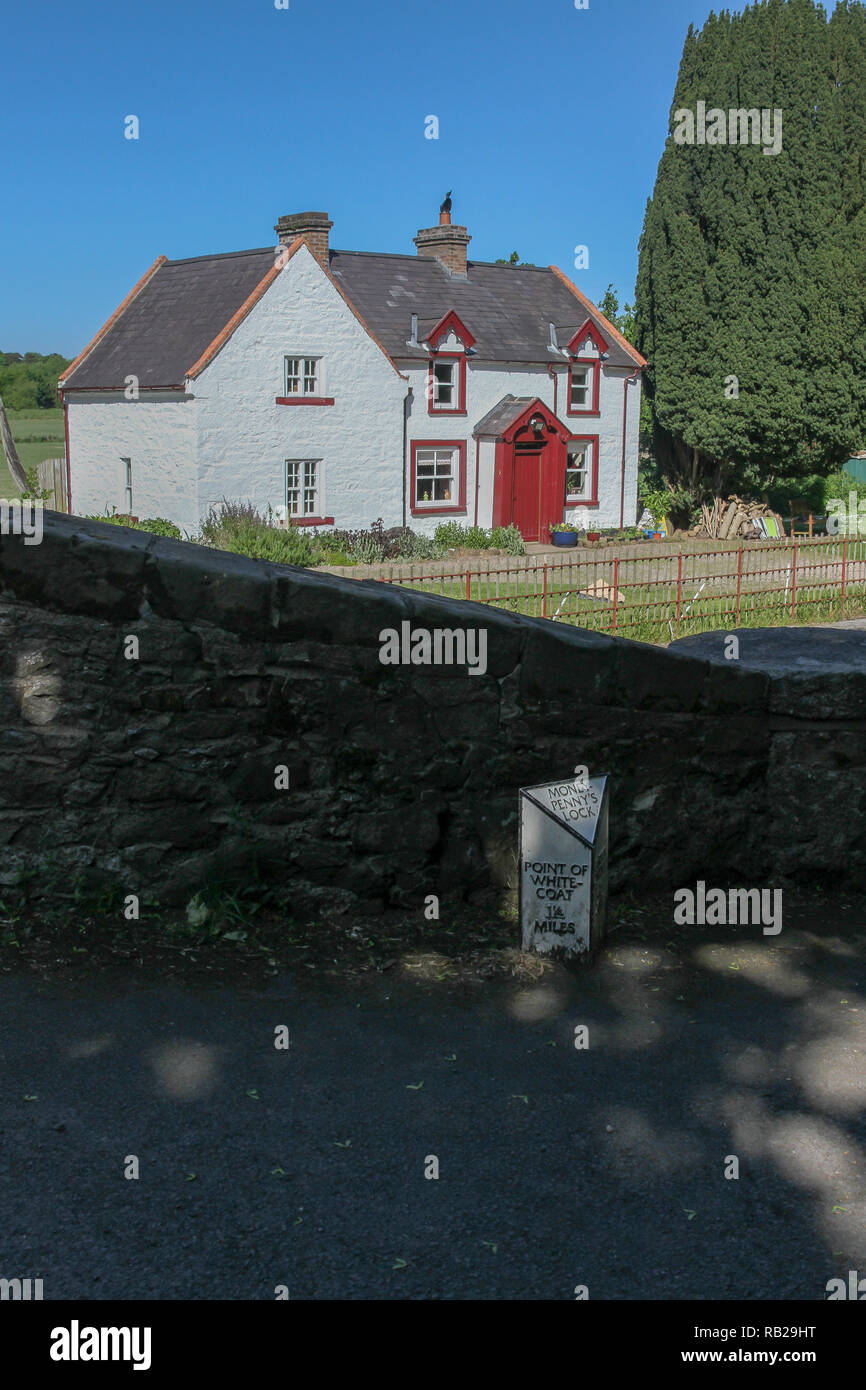 Distance marker on canal towpath with restored lockkeepers house at Moneypenny's Lock, Newry Canal, Northern Ireland. - Stock Image