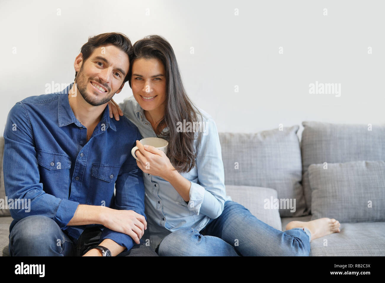 Isolated gorgeous smiling couple in denim on comfy couch - Stock Image