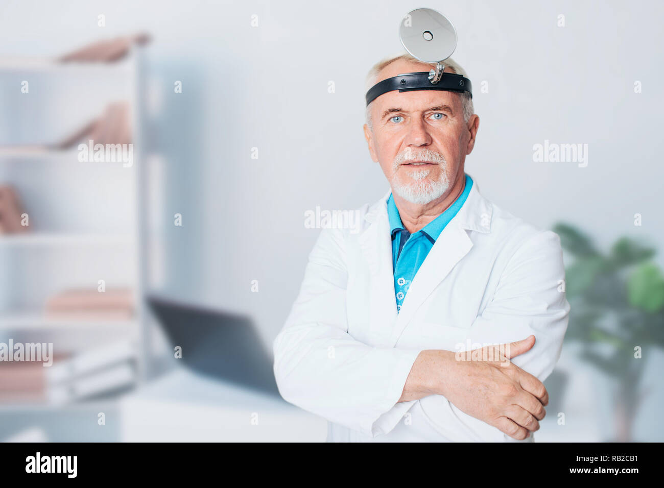 mature ENT doctor, elderly man standing at medical clinic Stock Photo