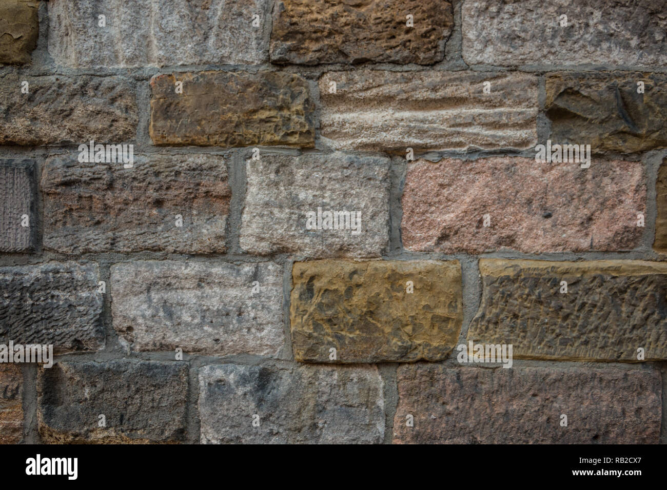Old wall of a historical building with different colored stones - Stock Image