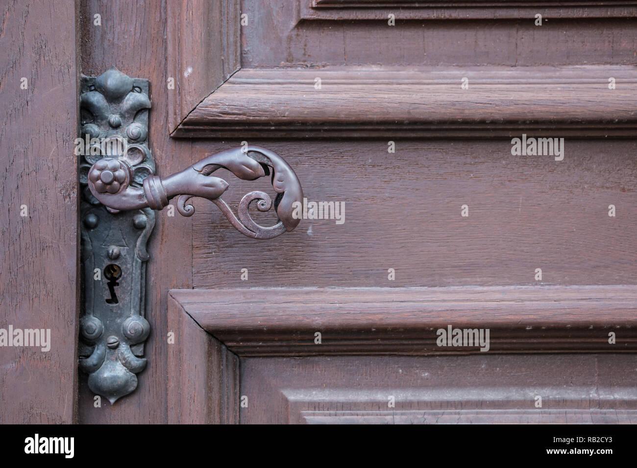 Iron door handle of an old door of a historical building - Stock Image