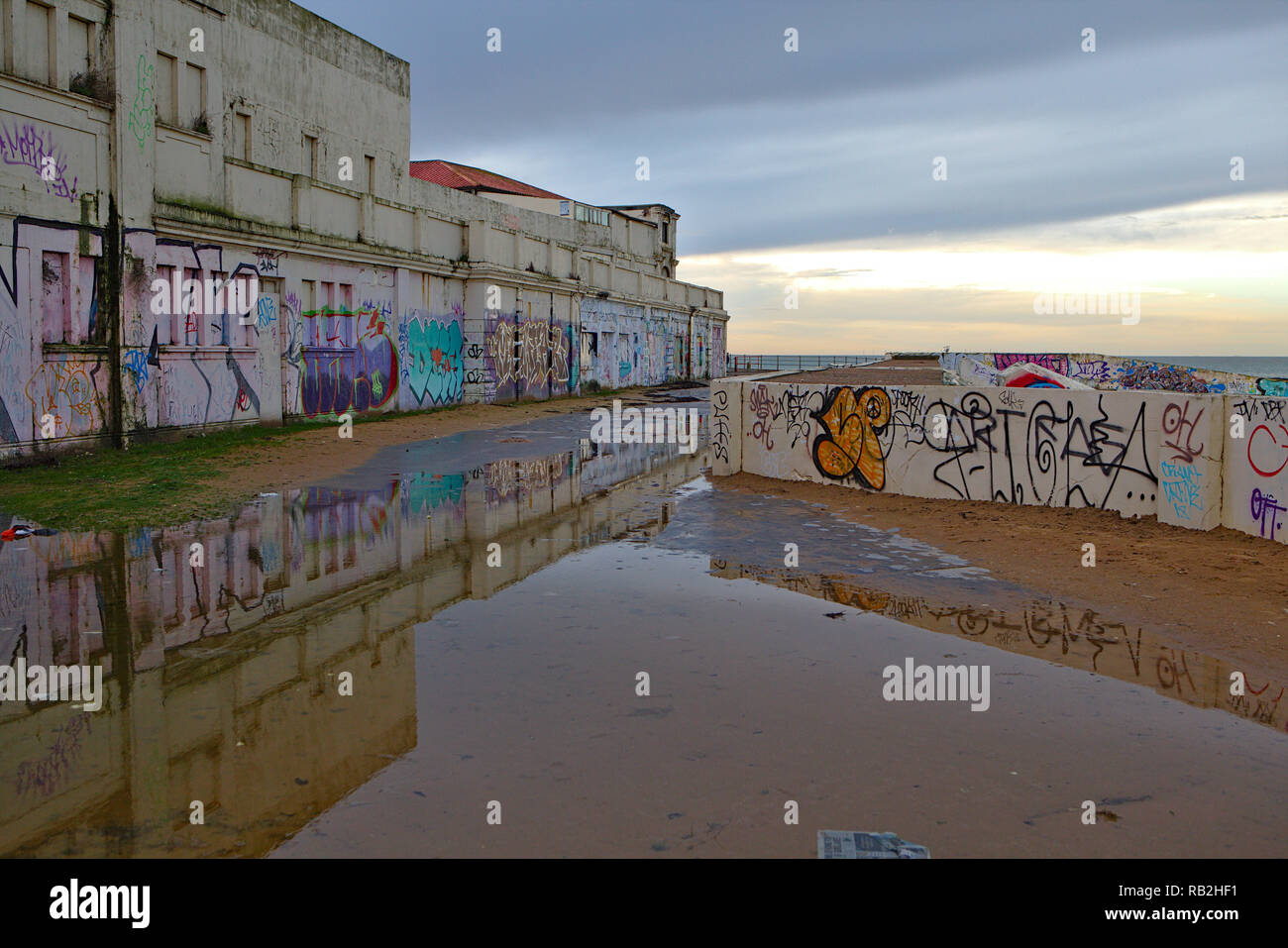 Graffiti on concrete walls on a rainy day by the sea in Margate - Stock Image