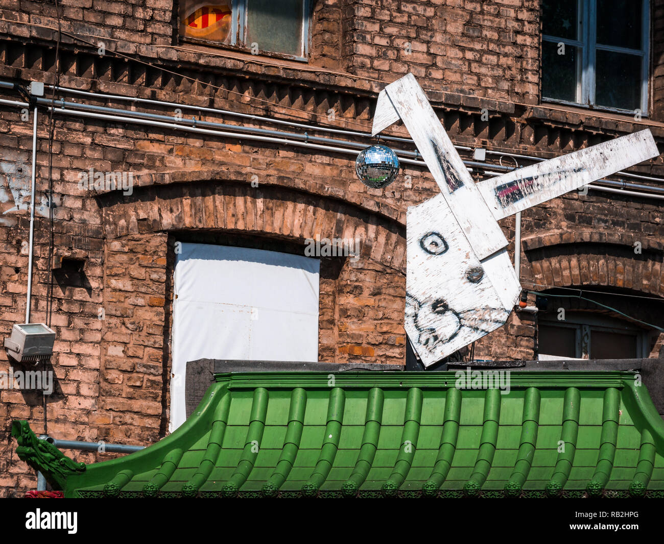 Berlin, Germany - May 21st 2018: Old industrial buildings decorated with street arts, green roof top and funny bunny - Stock Image