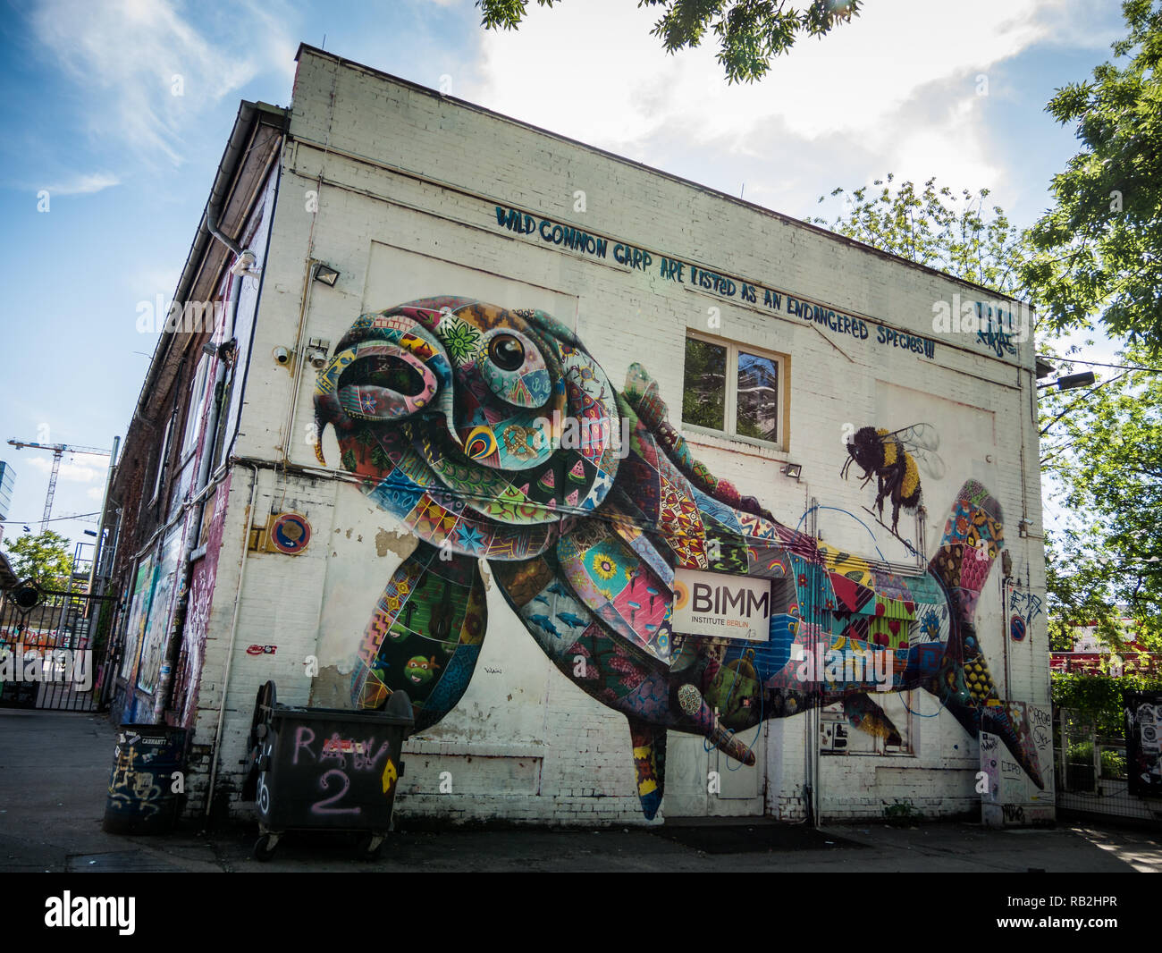 Berlin, Germany - May 21st 2018: Old industrial buildings decorated with colorful fish and bee graffiti, street arts - Stock Image
