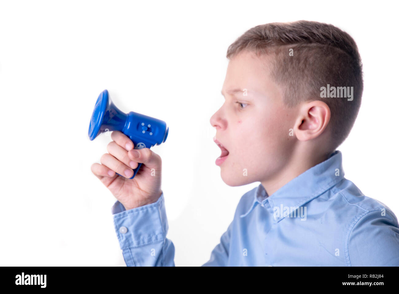 Boy shouting very loudly into a small blue megaphone with open mouth - Stock Image