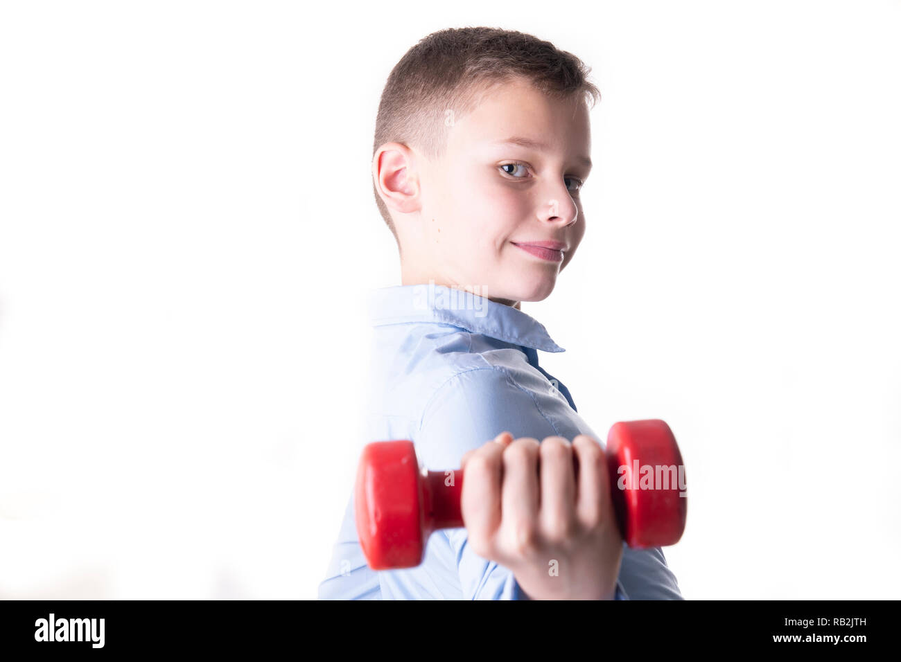 Boy with red dumbbell looks directly into the camera isolated on white background workout strength training - Stock Image
