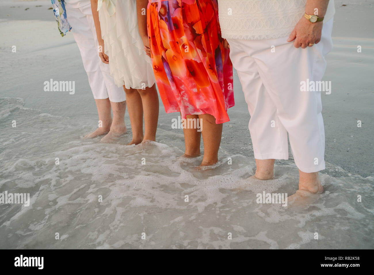 Family of Women Standing Facing the Ocean in Shallow Water Shoreline at the Beach on Vacation Outside in Nature - Stock Image