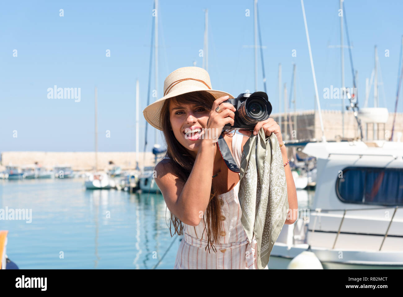 Traveling tourist woman on vacation in Heraklion Crete visiting the port. Lovely elegant girl takes pictures at the famous Mediterranean Venetian port - Stock Image