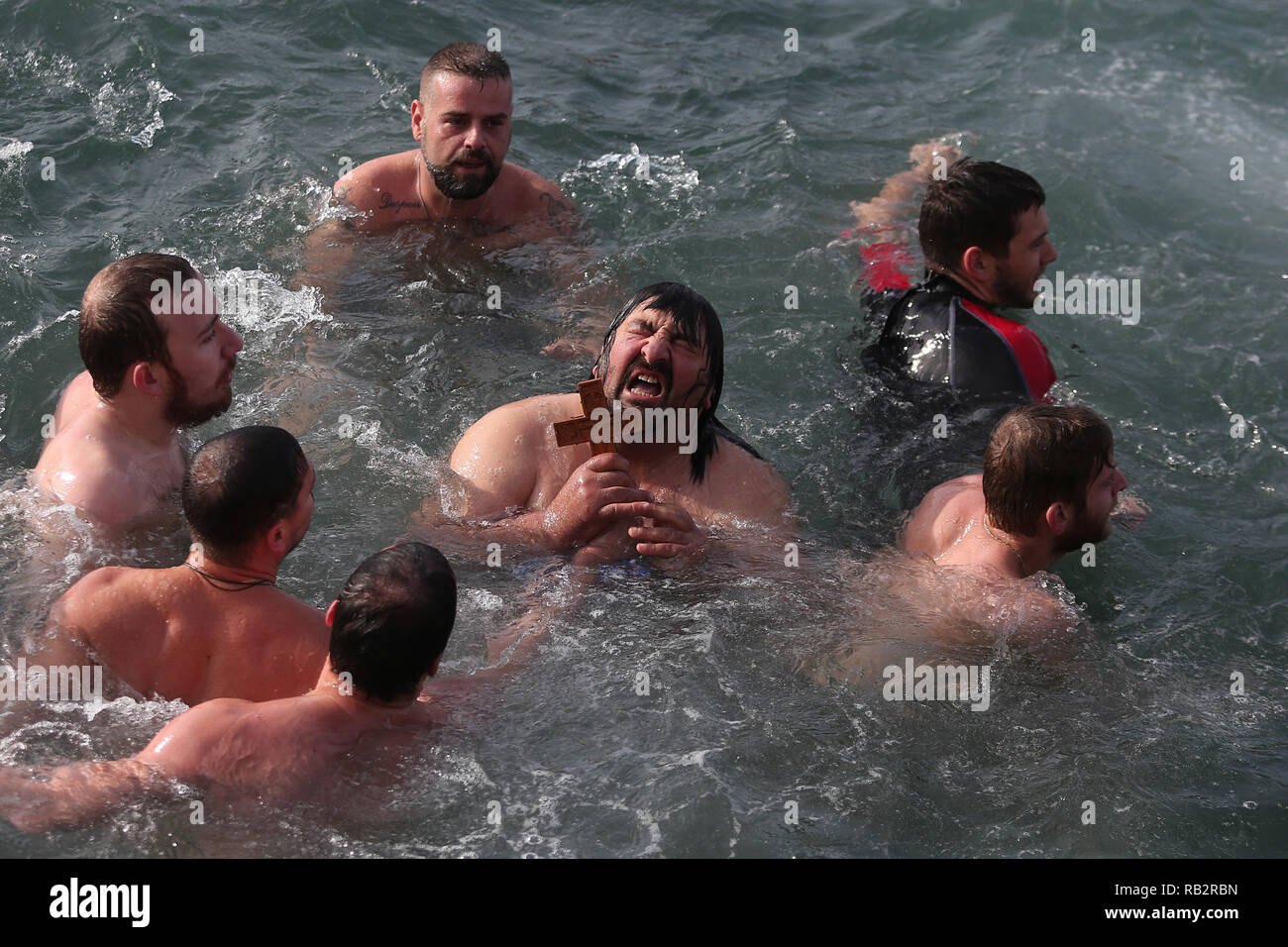 Thessaloniki, Greece. 6th Jan 2019. A man reacts after catching a wooden cross during an Epiphany water blessing ceremony at the northern Greek city of Thessaloniki. This ceremony marks the Epiphany Day celebrated every year in Greece as Christian Orthodox priests throw a cross into the water and swimmers race to retrieve it. Credit: Giannis Papanikos/ZUMA Wire/Alamy Live News Credit: ZUMA Press, Inc./Alamy Live News - Stock Image