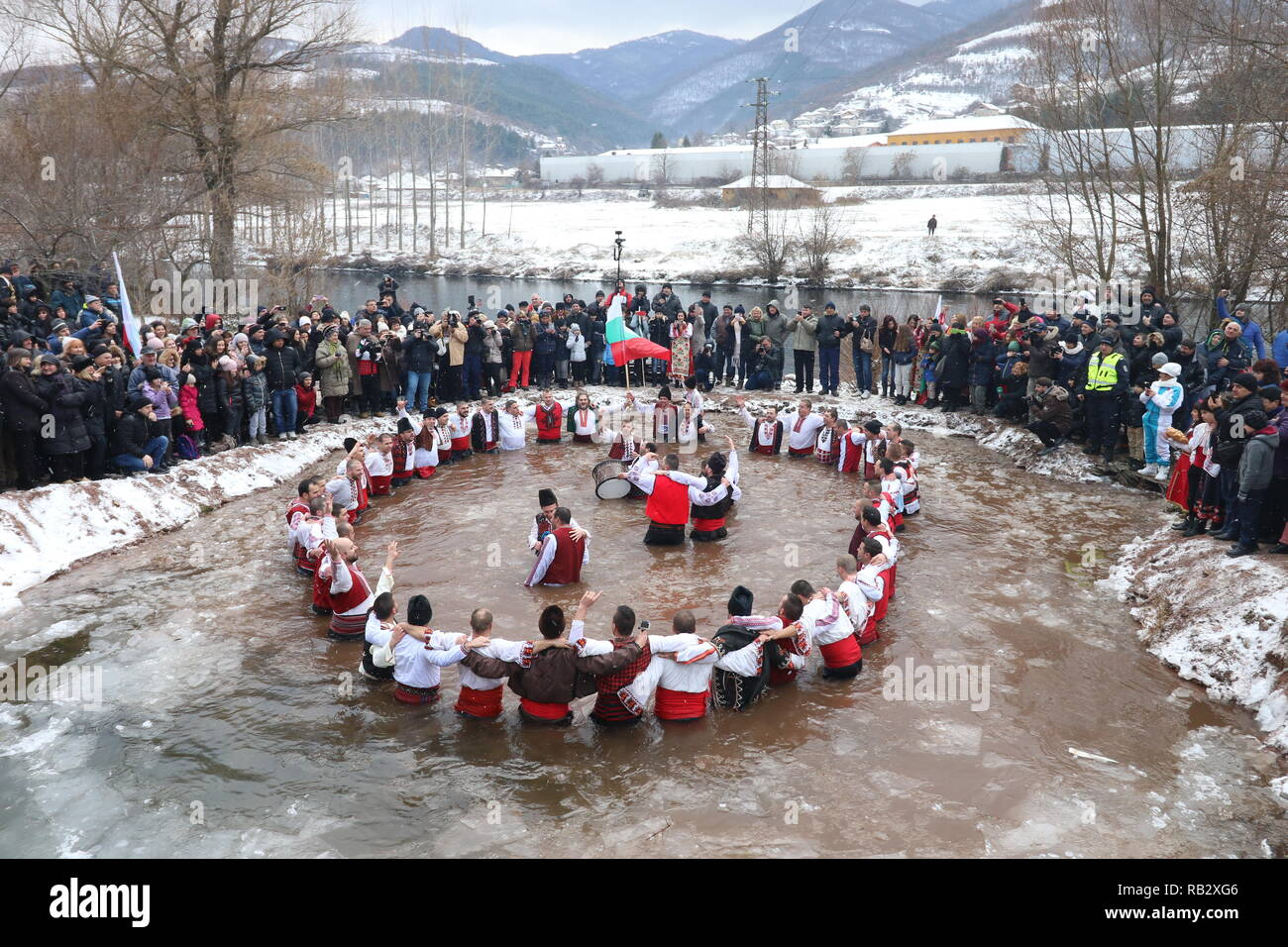 Zverino, Bulgaria. January 6, 2019: People perform the national dance 'Horo' in the icy waters of the river Iskar in the village of Zverino, during celebrations of the Epiphany day on 6 January 2019. Credit: GeorgiD/Alamy Live News - Stock Image