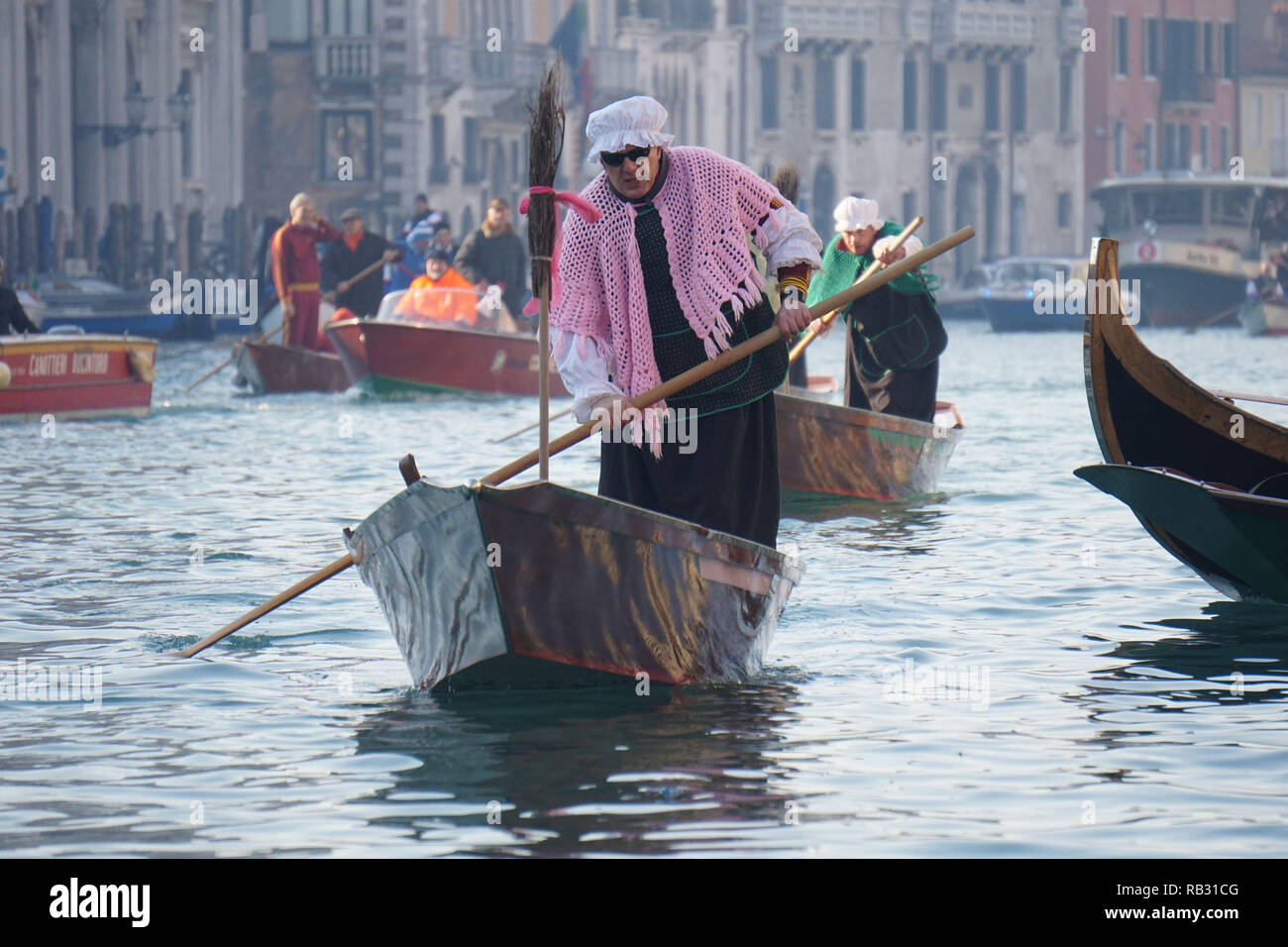 Venice, Italy. 6th January, 2019. The Venetian rower Francesco Guerra, nickname 'Malaga', marked by the pink shawl, while rowing in the first position, during the traditional rowing boat race, on the Grand Canal, between rowers dressed as Befane, on 6 January 2019. in Venice, Italy. © Andrea Merola / Awakening / Alamy Live News - Stock Image