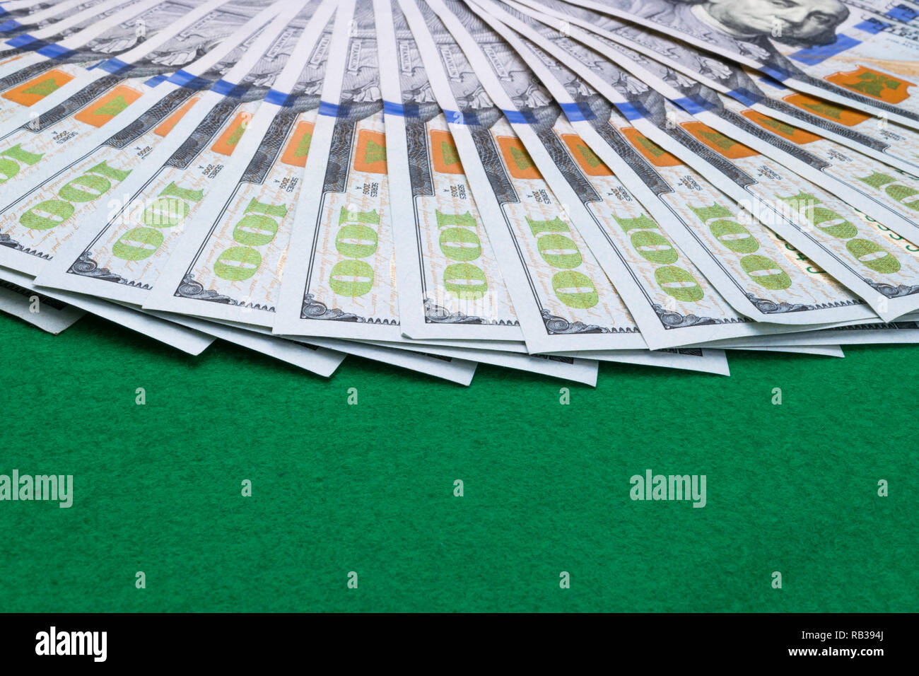 Stack of one hundred dollar bills. Stack of cash money in hundred dollar banknotes. Heap of hundred dollar bills on green poker table. Game concept - Stock Image