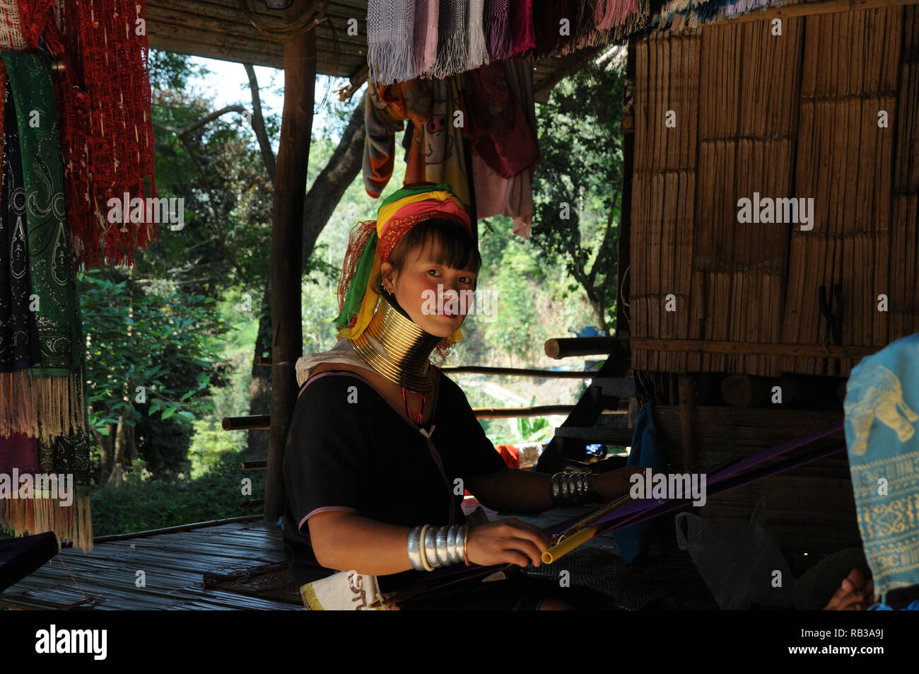 Young Kayan Lahwi woman weaving in a remote mountain village, Chiang Mai Province, Thailand Stock Photo