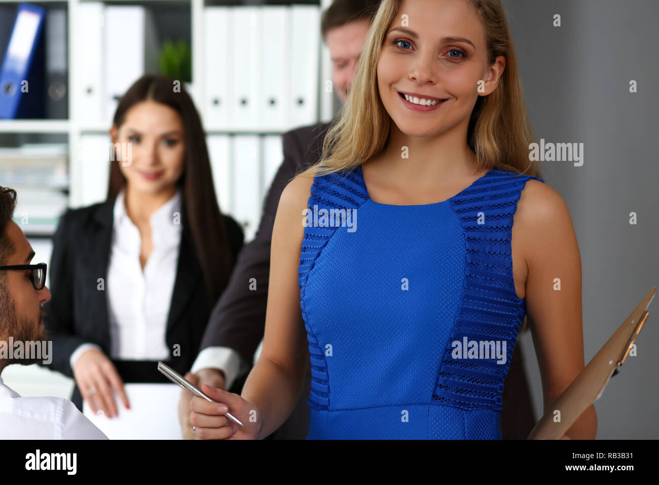 Beautiful smiling clerk girl wearing blue sundress - Stock Image