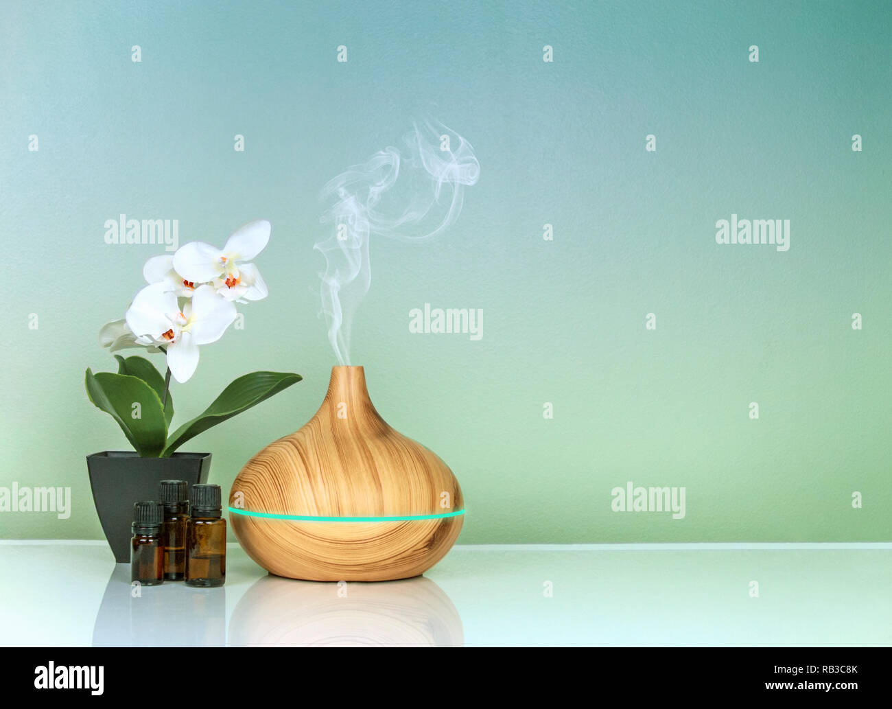Electric Essential oils Aroma diffuser, oil bottles and flowers on green gradient surface with reflection. - Stock Image