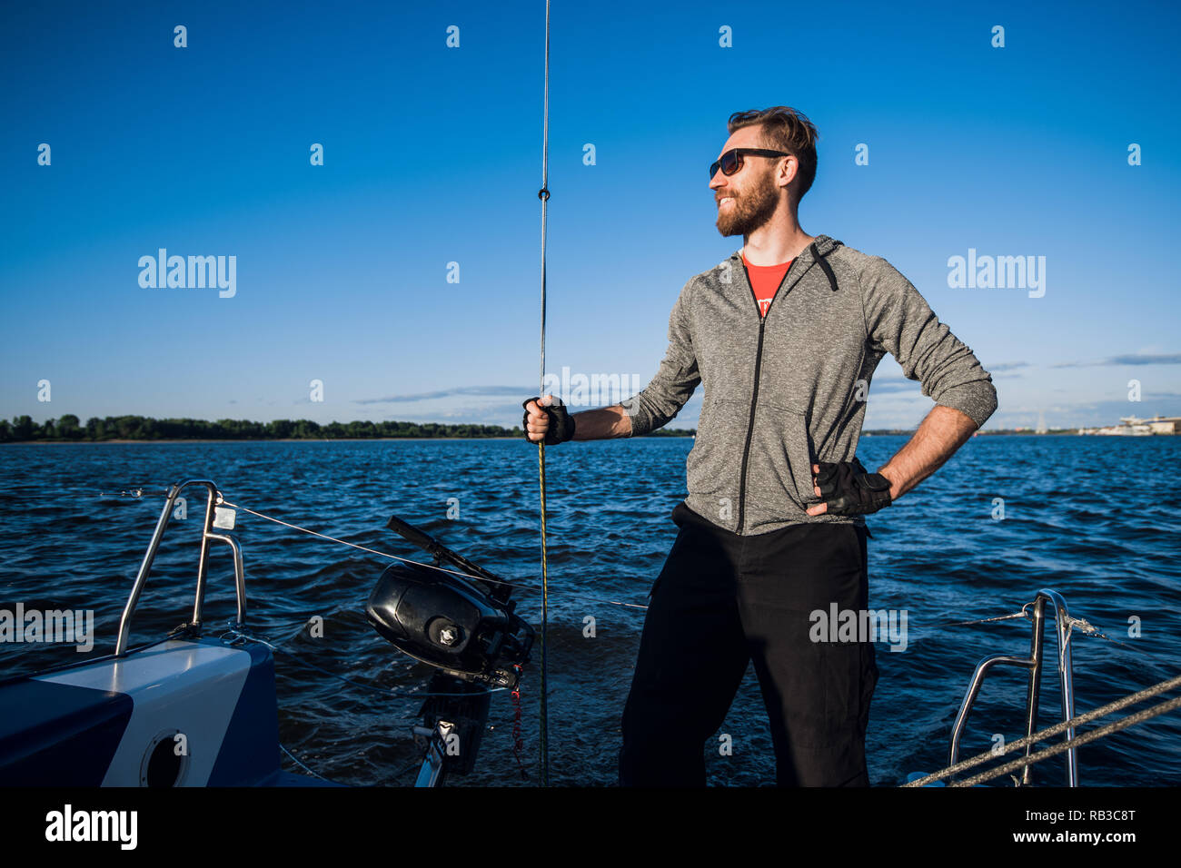 Young man wearing sunglasses standing on yacht stern and enjoying perfect autumn day under sails - sailing holidays concept Stock Photo
