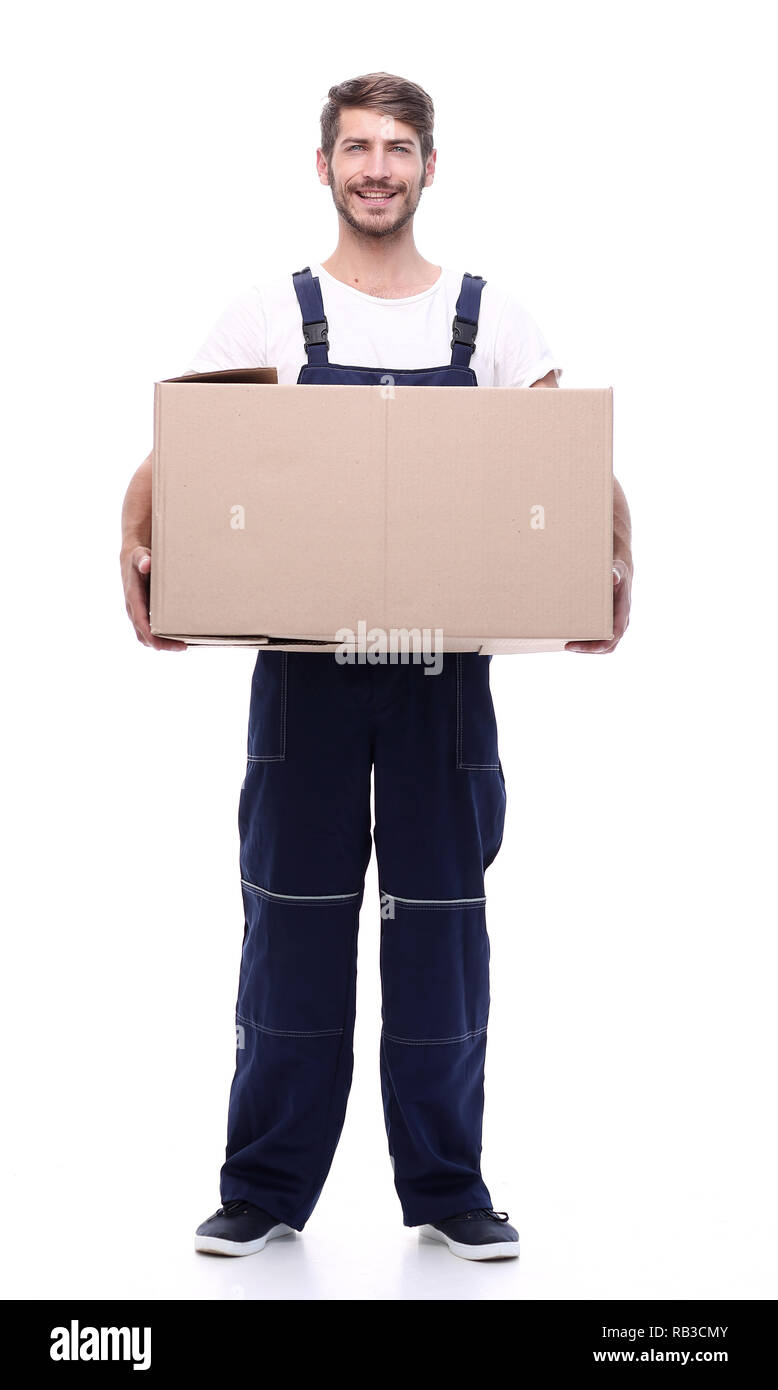 man in a jumpsuit holding a large box - Stock Image