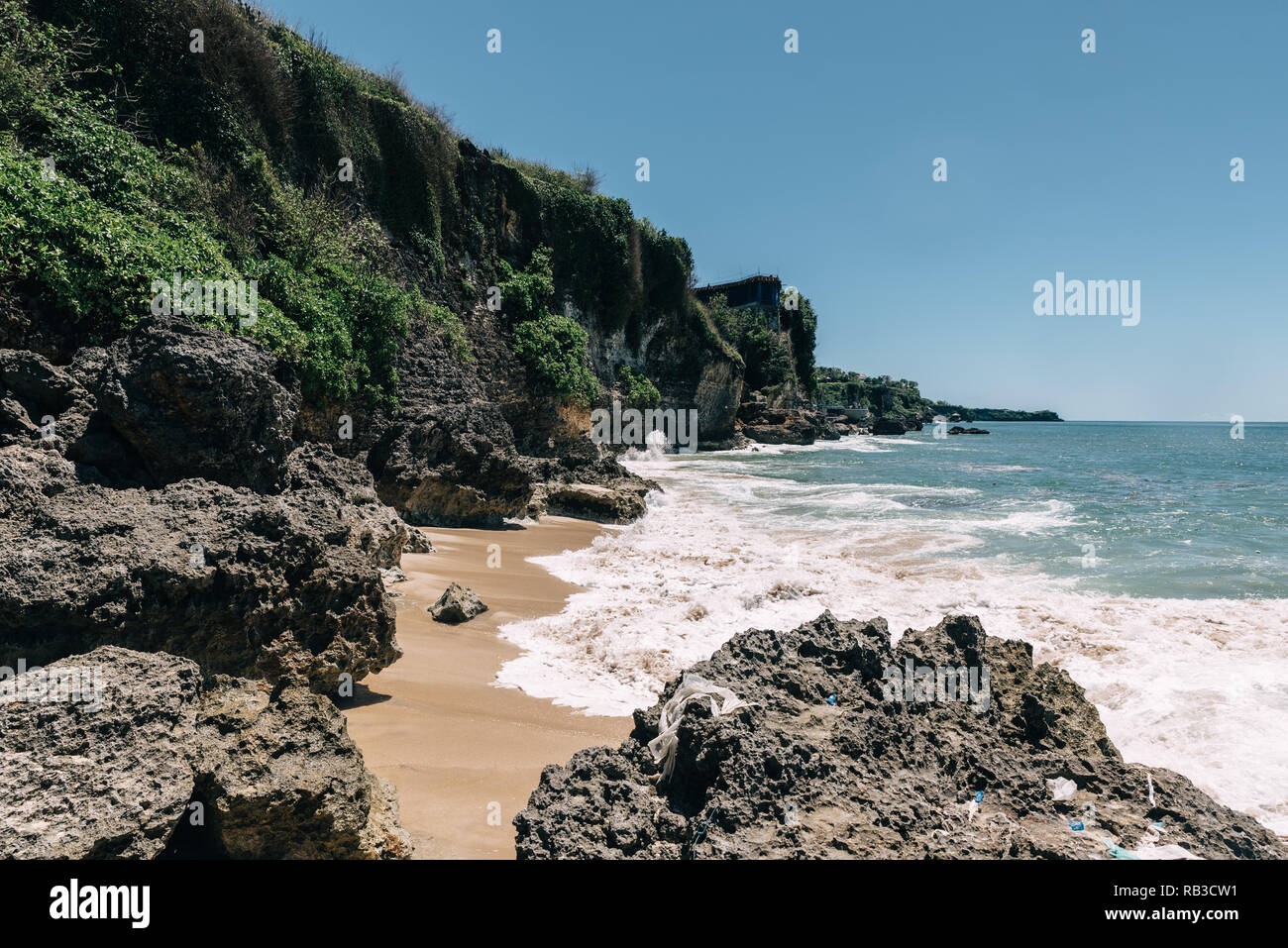 Beach on Bali, Indonesia called Pantai Tegal Wangi. Sunny clear weather. Big cliffs with houses, blue sky and ocean with waves - Stock Image