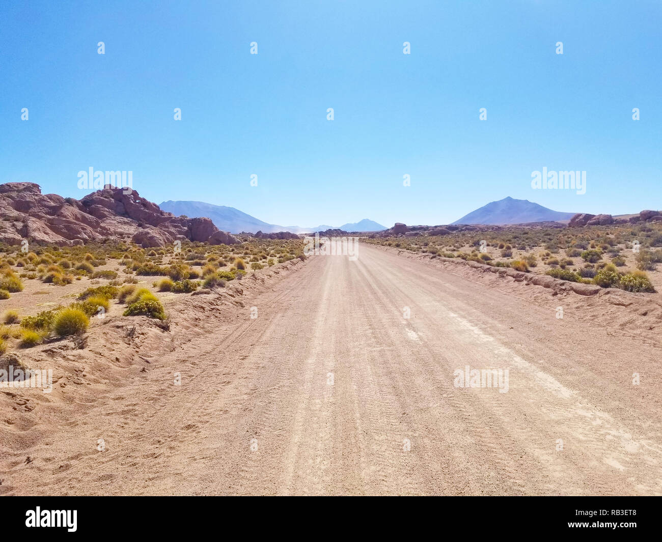 Desert road with mountains in the distance. Rocky mountains and little vegetation. Stock Photo