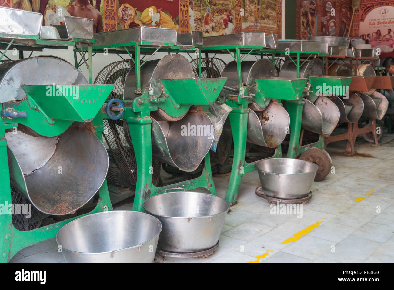 A row of metal cacao roasters with metal catching bowls on the ground, in Oaxaca, Mexico - Stock Image