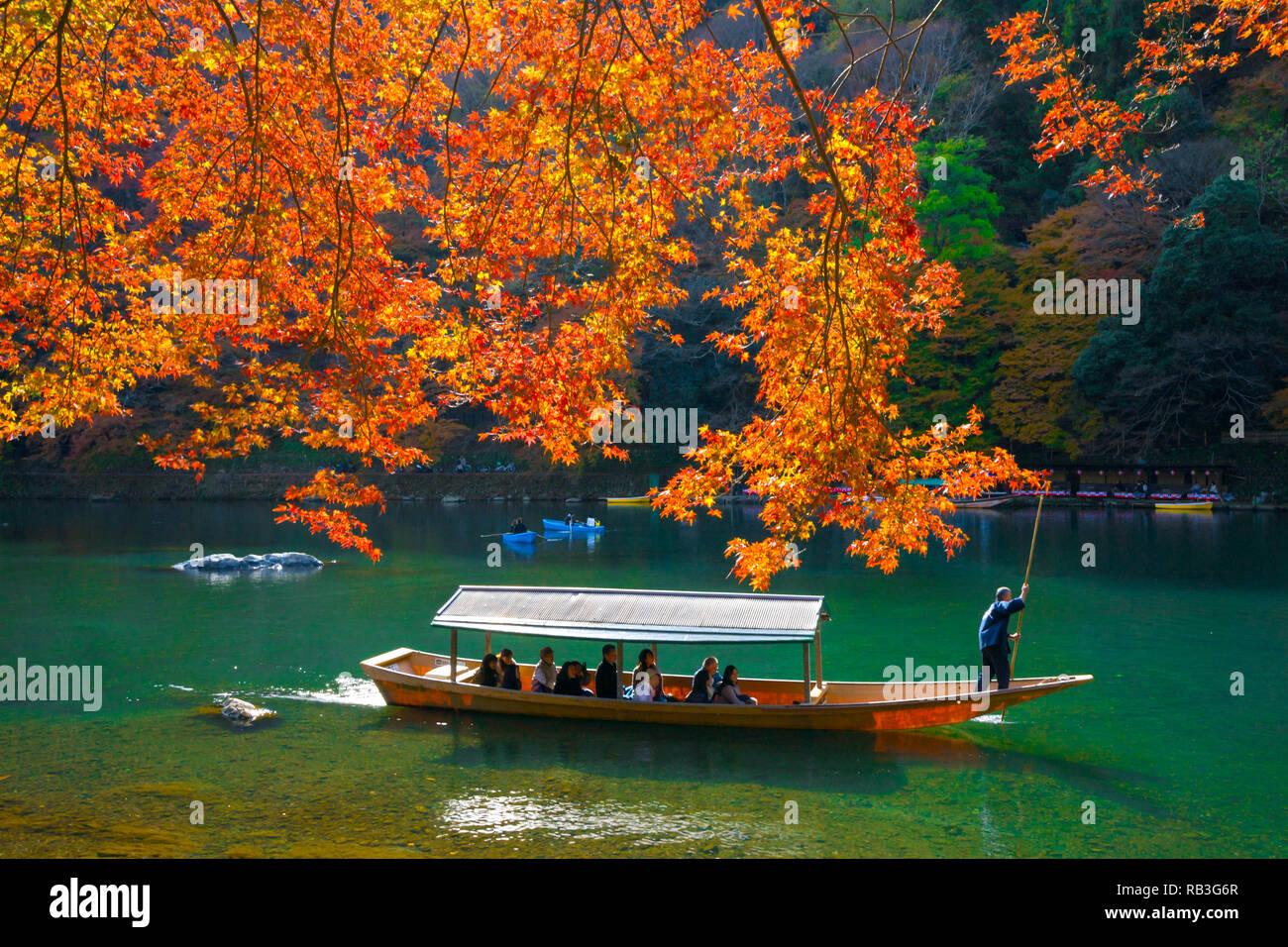 Pleasure boat at Arashiyama in Autumn season.The famous ways to explore Arashiyama is by renting a boat. - Stock Image