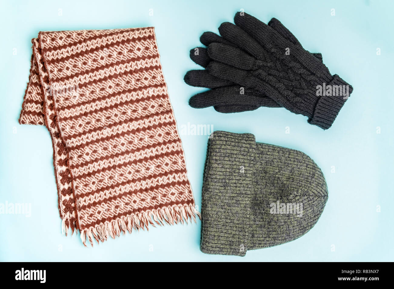 Top view of winter clothing accessories for outdoor use. Knit-hat beanie, winter gloves and wool scarf neatly organised on pale blue background - Stock Image