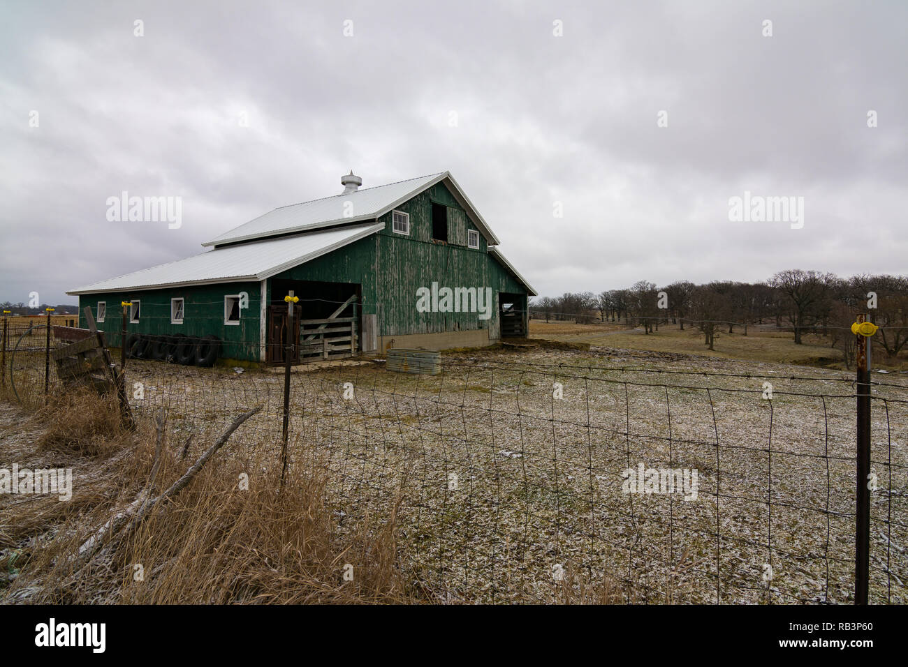 Vintage green barn after a light snow dusting.  Millbrook, Illinois, USA - Stock Image