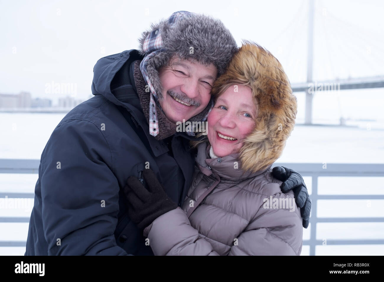 Portrait Of Elderly Couple Having Fun Outdoors In Winter Smiling