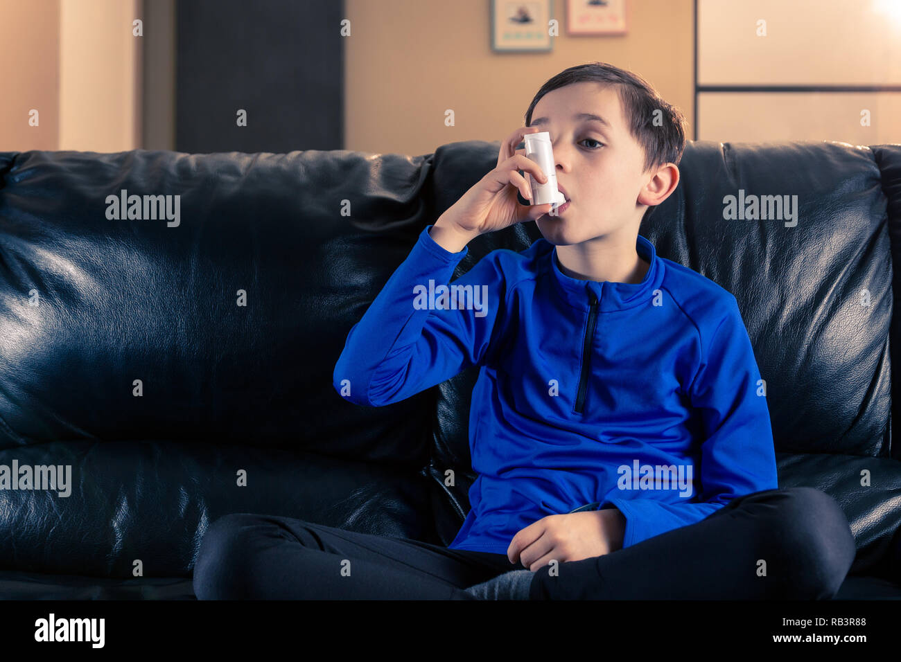 8 year old boy wearing sportive clothing inhaling with an asthma inhaler sitting in sofa. Concepts : health, illness, doping - Stock Image