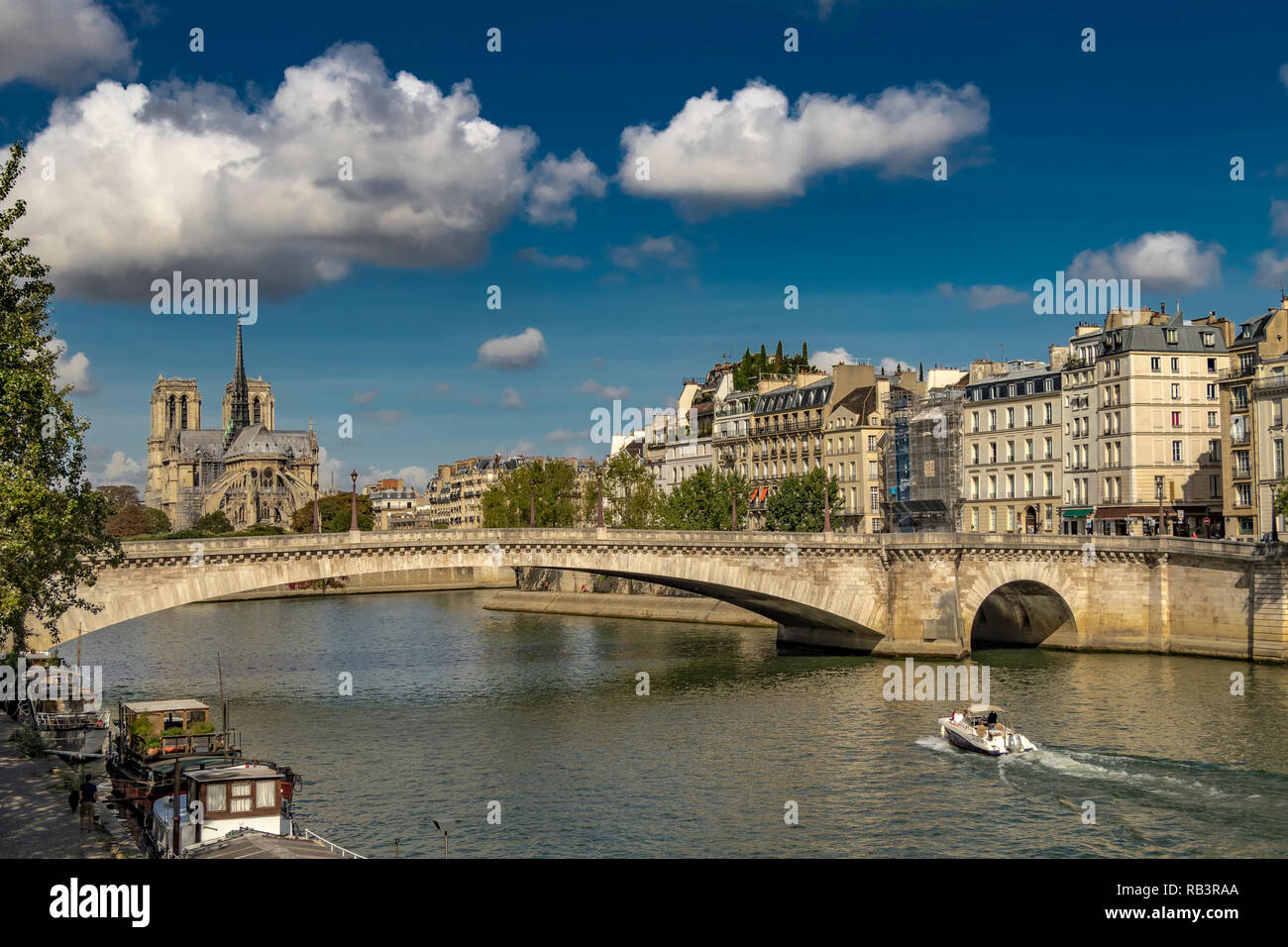 Pont De La Tournelle spans the River Seine with Notre Dame Cathedral and Île Saint-Louis in the background  on a warm summers day ,Paris ,France - Stock Image