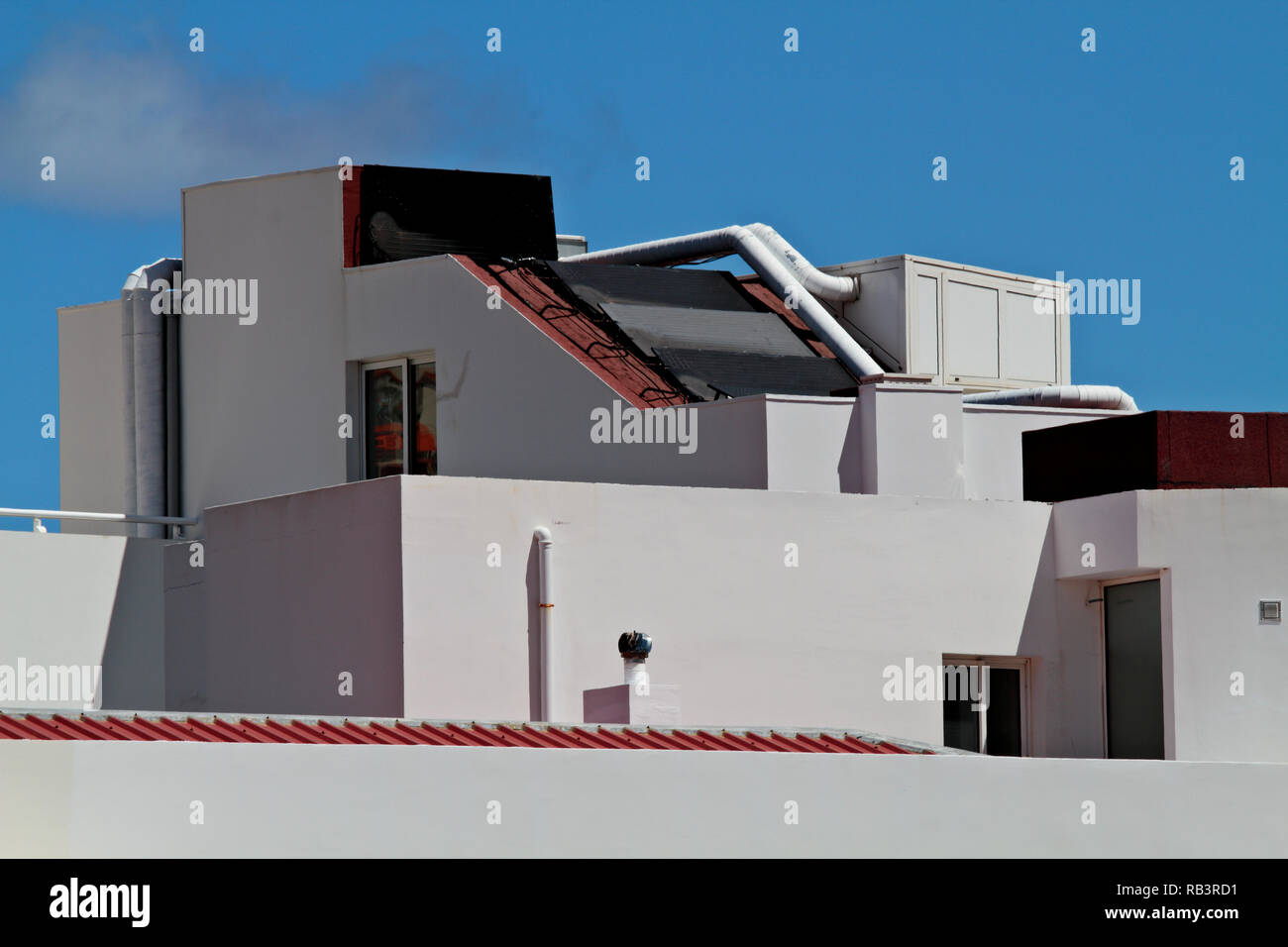 White house with solar panels on the roof top. Sun shines high in the sky Stock Photo
