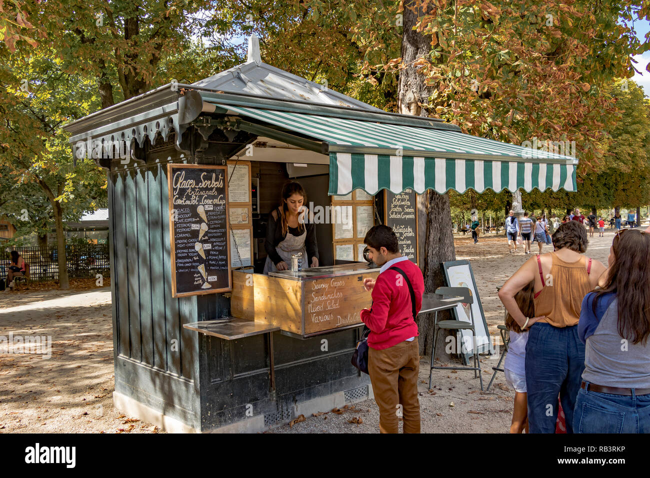 A line of People queueing at a refreshment kiosk on a summers day to buy refreshments from the kiosk vendor  in Jardin du Luxembourg ,Paris,France - Stock Image