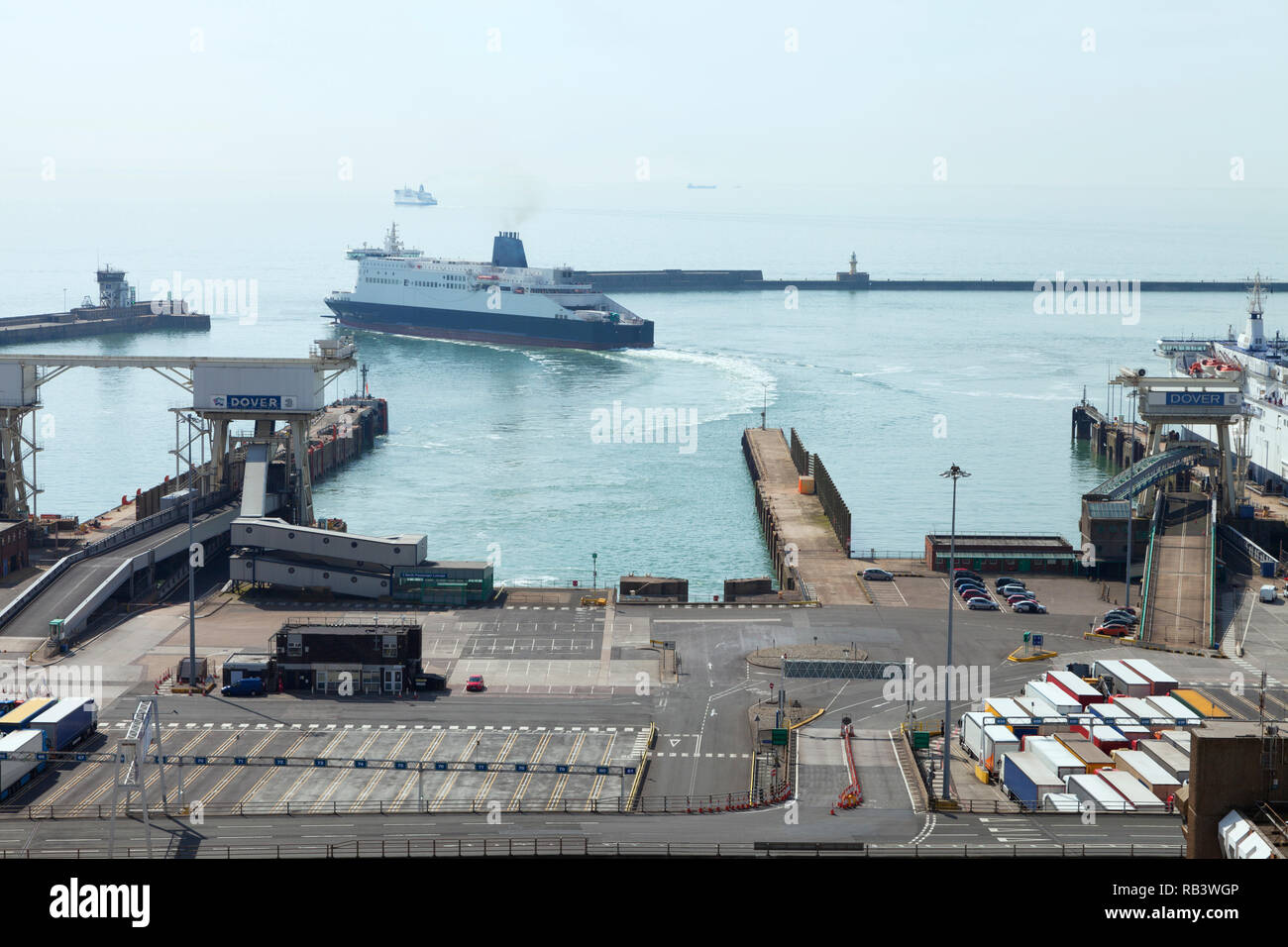 Ferry entering Port of Dover terminal. Lorries and cars waiting for channel crossing, Dover, Kent, UK, on a foggy summer day . Stock Photo