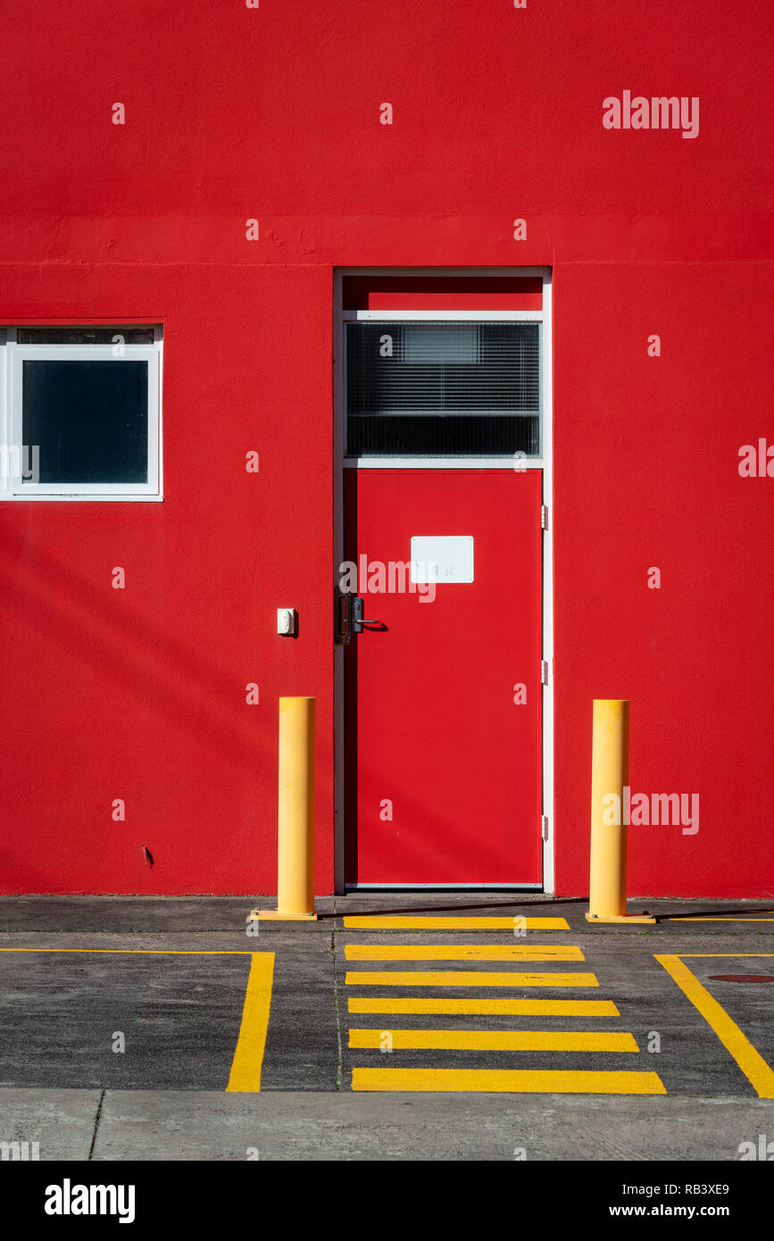 A bright red building with a red door and leading yellow lines painted on the asphalt - Stock Image
