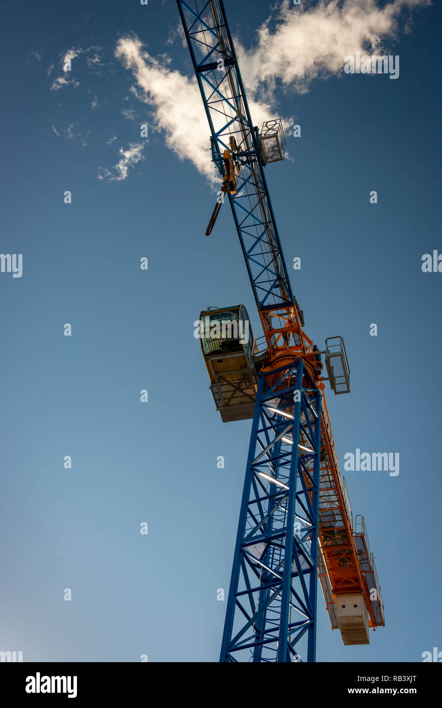 Construction crane partially silhouetted against a blue sky and bright cloud - Stock Image