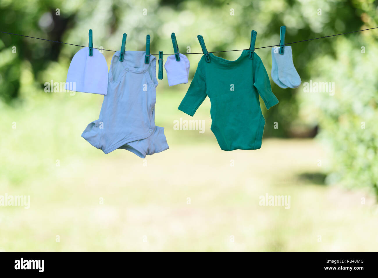 Baby clothes on clothesline drying in garden. Newborn childhood concept - Stock Image