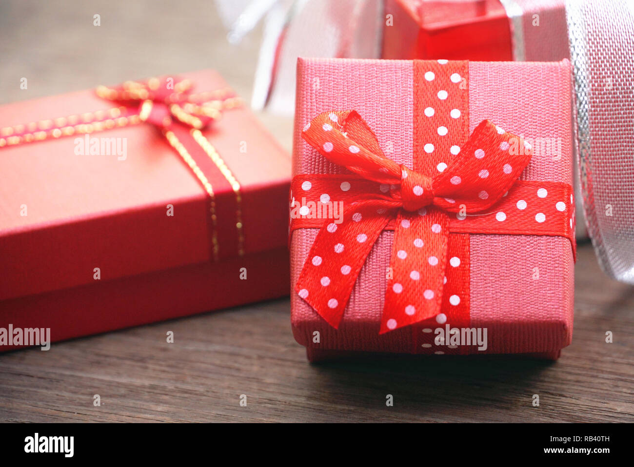 Red gift box on wood table - Stock Image