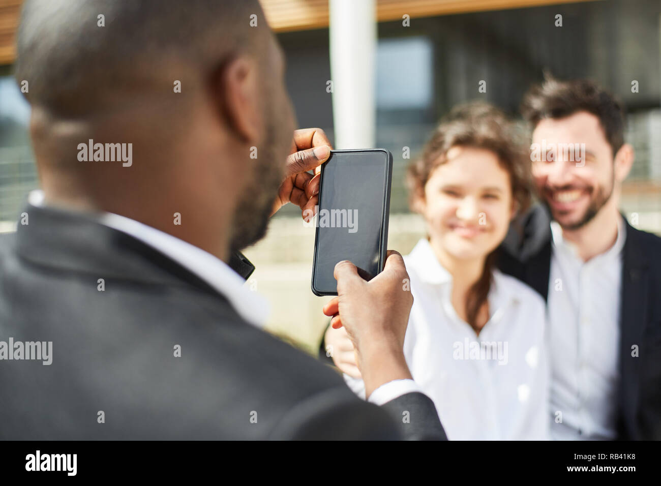 Business man photographs young happy couple with the smartphone - Stock Image