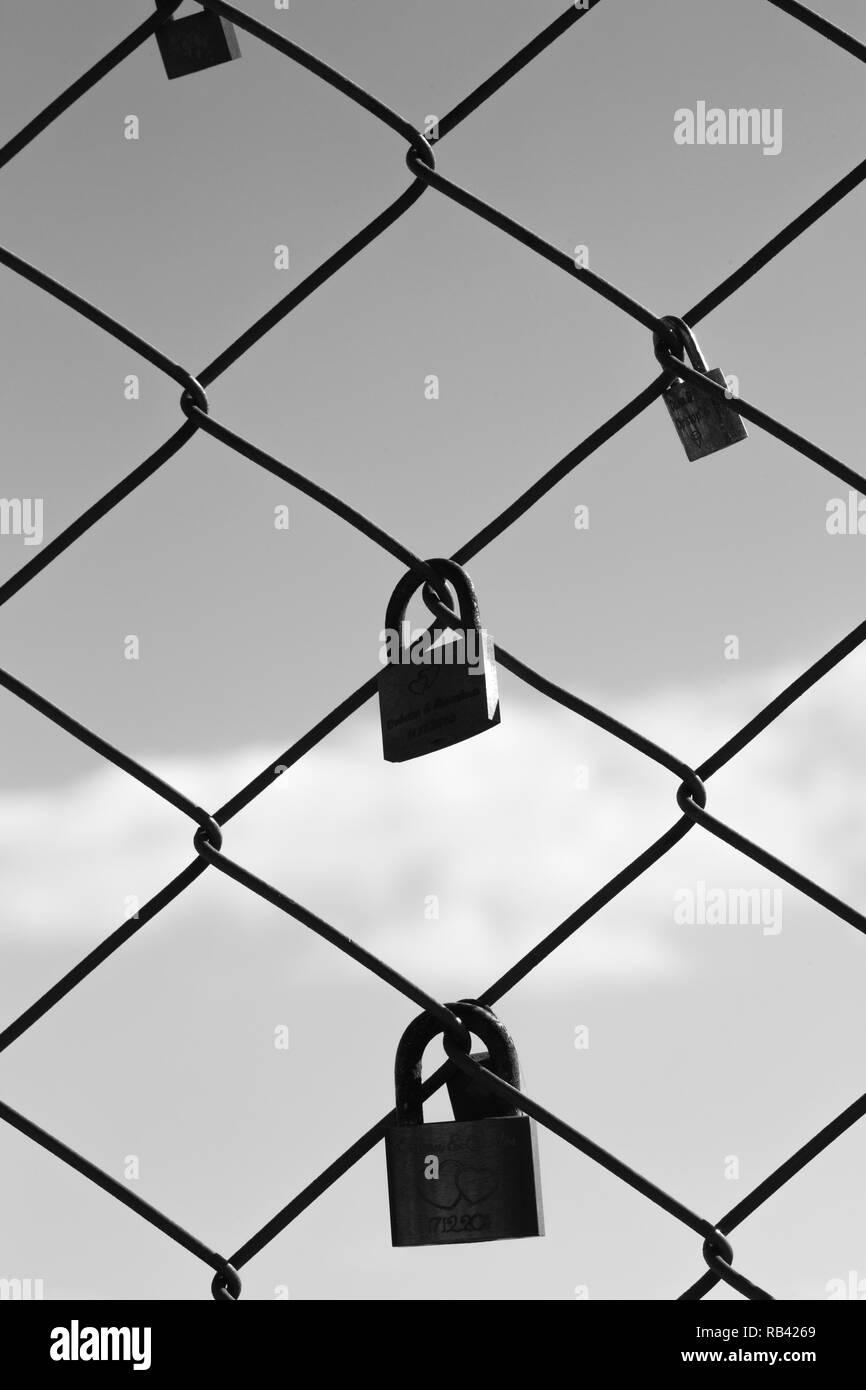 Black and white photography of weding padlocks on the fence of Santa Justa elevator, Lisbon, Portugal Stock Photo