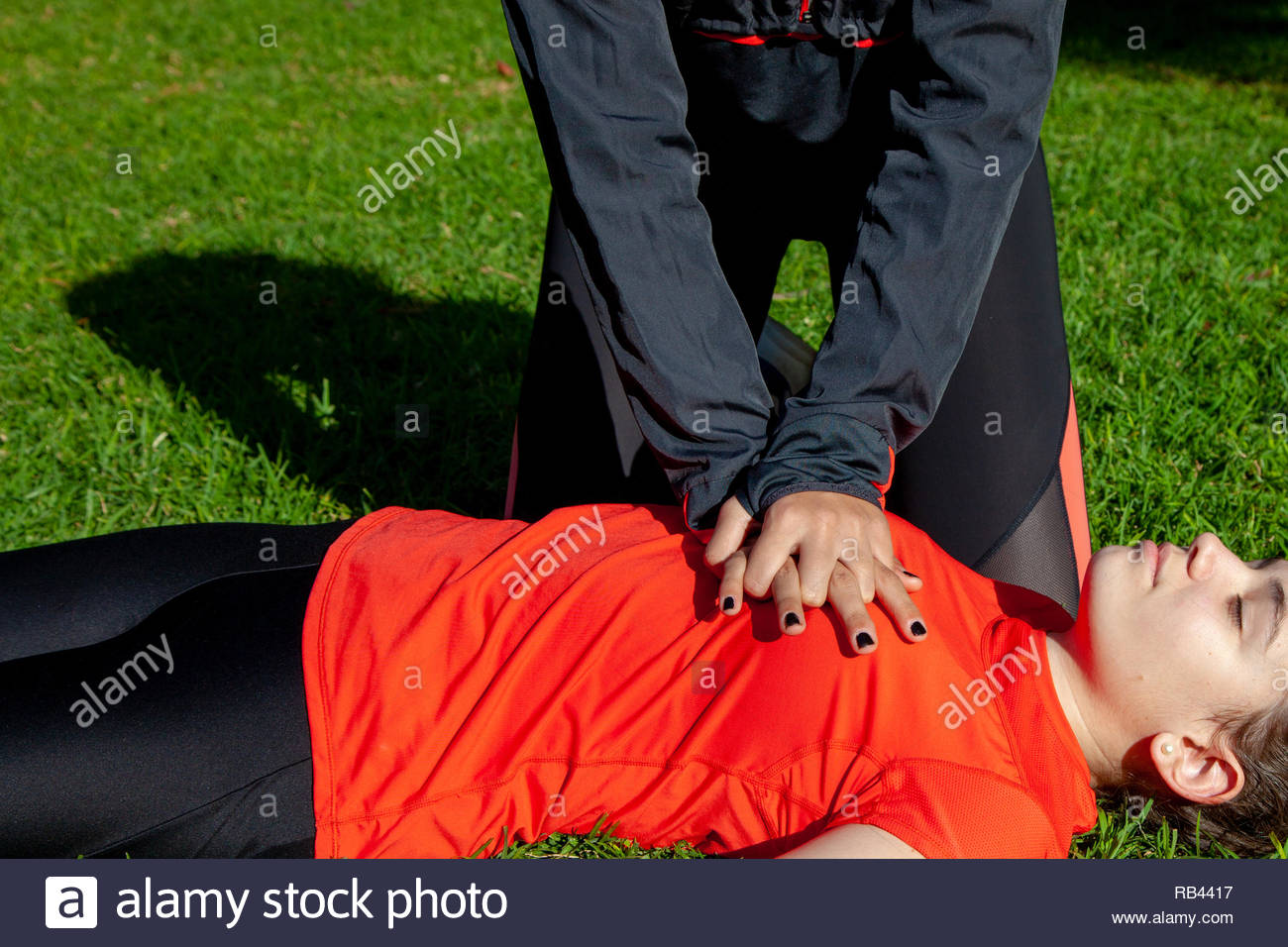 Two young girls practicing cardiopulmonary resuscitation manoeuvres in an open-air park - Stock Image