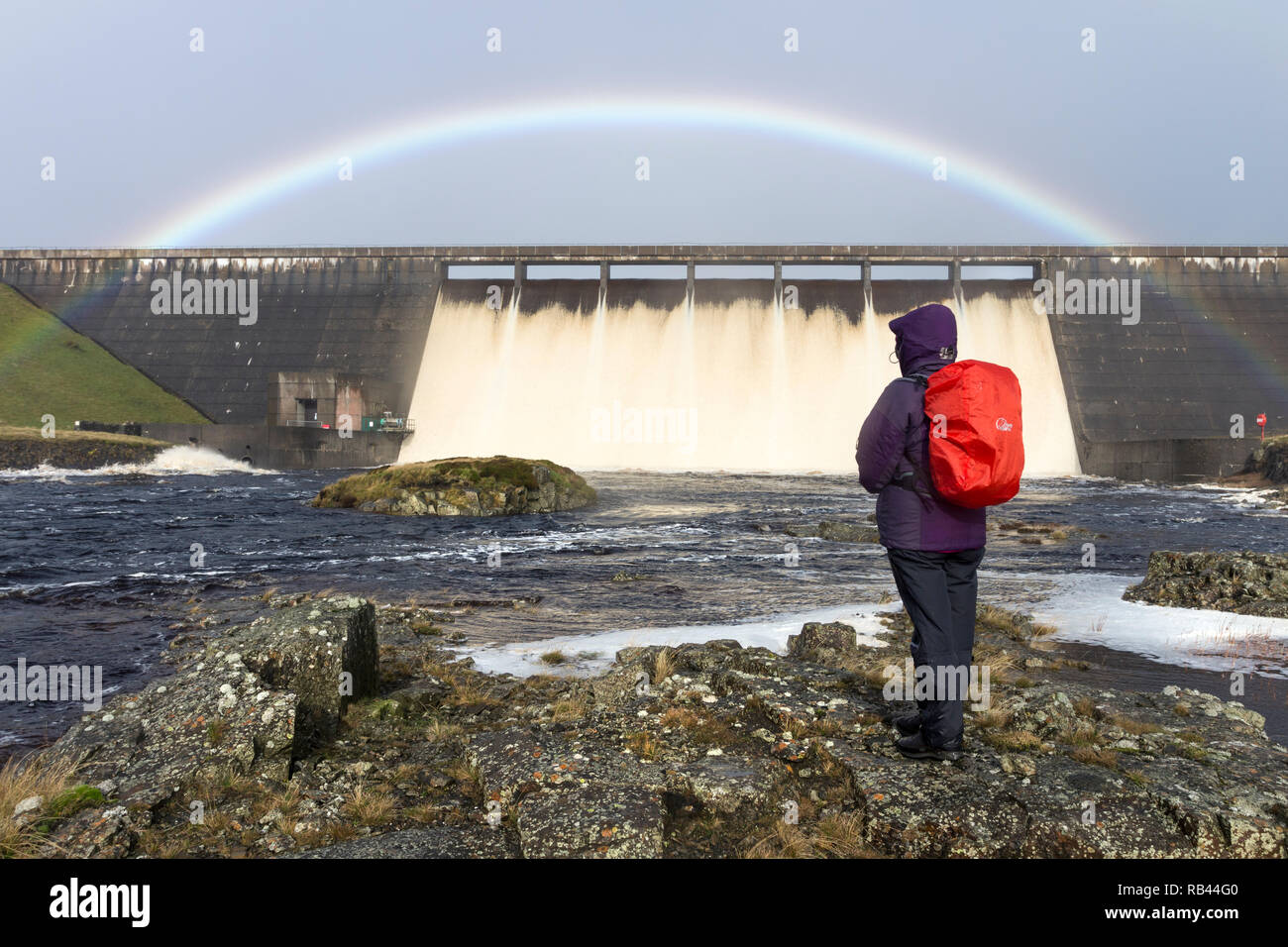 A Walker Enjoys the Spectacle of Cow Green Reservoir Overflowing Due to Heavy Rains Brought by Storm Brian on 22nd October 2017, Teesdale Co Durham - Stock Image