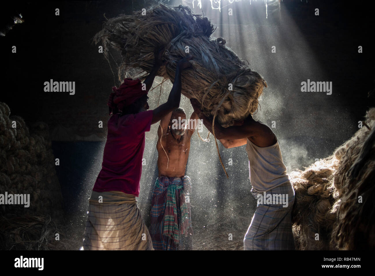 Narayanganj, Bangladesh. 6th Jan 2019. Jute mill workers seen helping each other while working. Bangladesh is known for its Jute. In recent years Bangladesh and many other countries considered jute as a new possibility to replace many daily goods, notably making bags out of jute to replace plastics Credit: SOPA Images Limited/Alamy Live News Stock Photo