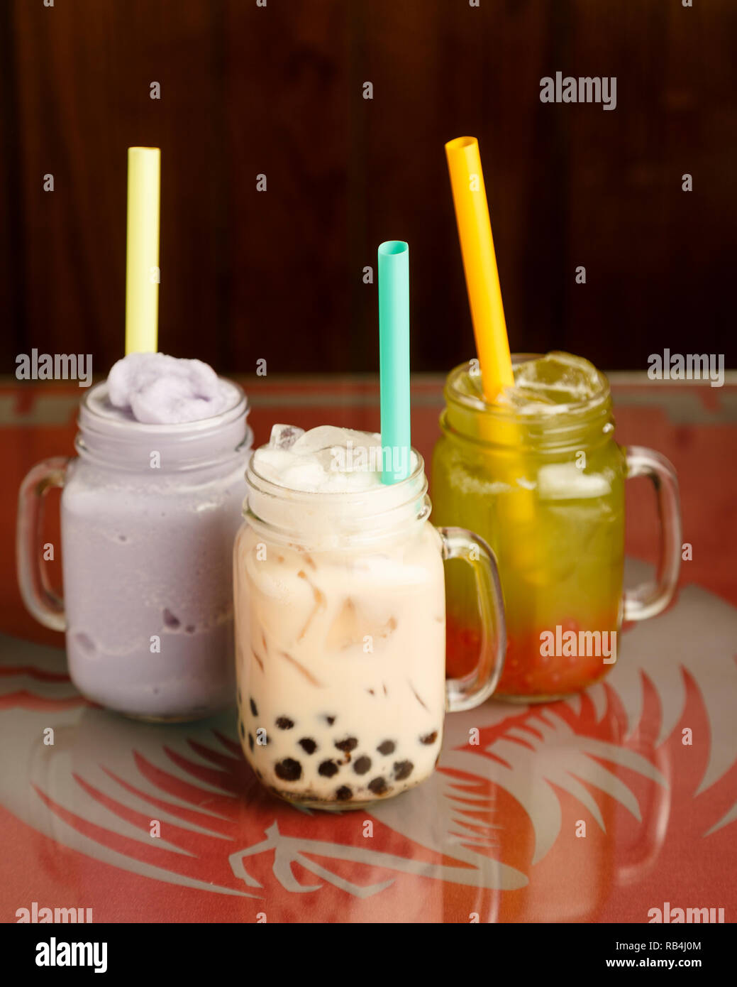from left to right: taro smoothie, black milk tea with honey boba, honeydew green tea with strawberry popping boba on a table in a Chinese restaurant Stock Photo