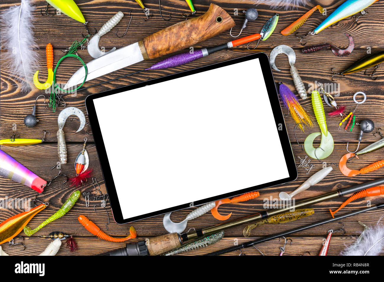 Fishing rod, tackles and fishing baits, reel on wooden board background with tablet computer isolated white screen, empty space for text - Stock Image