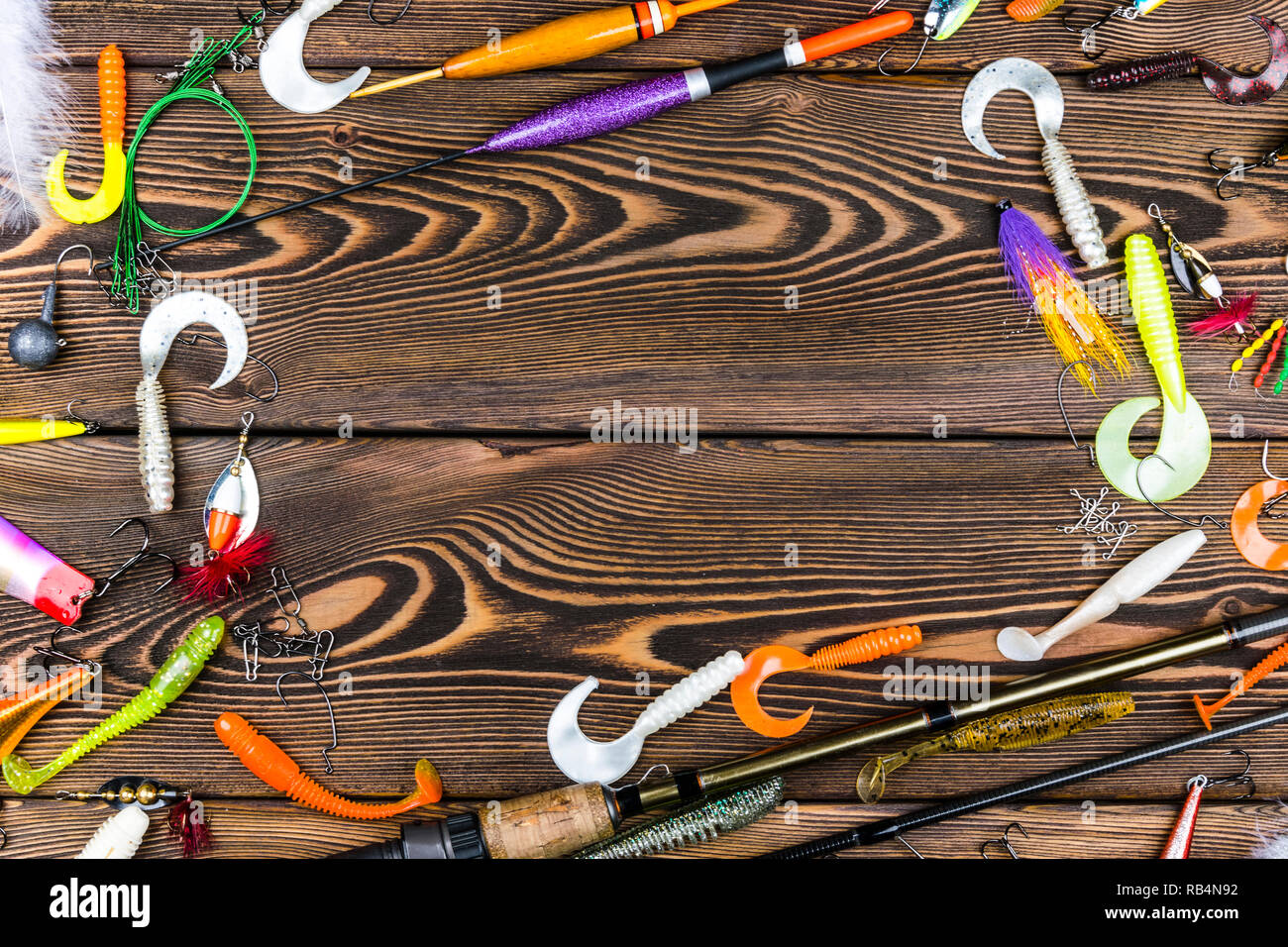 Sankt-Petersburg, Russia, June 16, 2017: Fishing rod, tackles and fishing baits, reel on wooden board background - Stock Image